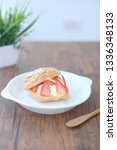 Small photo of Fresh choux cream pastry or cream puff with cream and strawberry