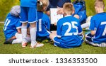 Small photo of Coach Coaching Kids Soccer Team. Youth Football Team with Coach at the Soccer Stadium. Boys Listening to Coach's Instructions Before Competition. Coach Giving Team Talk Using Soccer Tactics Board