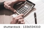 male hand using calculator ... | Shutterstock . vector #1336534310