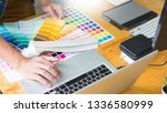 Stock photo graphic designer team working on web design using color swatches editing artwork using tablet and a 1336580999