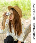 Small photo of Women tourists women white skin lovely brown hair wearing a basketry hat wear white shirt wearing black pants in hand have a camera traipse photograph nature.