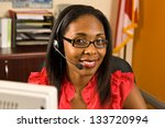 A beautiful African American receptionist wearing a headset and glasses smiling as she looks toward the camera - stock photo