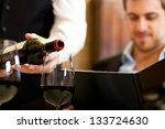 Waiter Pouring Red Wine To A...