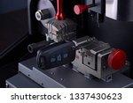Small photo of Close view of key copying machine with key. Duplicate machine make new key. Locksmith theme. Blank keys for cutting. Black modern car door opener.
