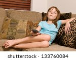 Young female child holding a remote while watching television - stock photo