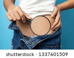 Small photo of Women Show off the belly after birth. Stretch Marks on blue background