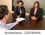 Young African American couple about to sign papers - stock photo