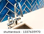 Stock photo new modern faucet and kitchen sink closeup with countertop blue vibrant backsplash and shiny clean 1337635970