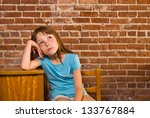 Young girl leaning on school desk thinking - stock photo