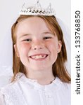 A close-up/head shot, shot straight on, of a young girl smiling in her First Communion Dress and Veil - stock photo