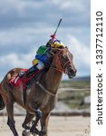 Small photo of Galloping race horse sprinting on the beach, Jockey holding whip up