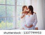 daughter kisses a pregnant... | Shutterstock . vector #1337799953