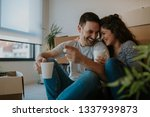 young happy couple moving in... | Shutterstock . vector #1337939873