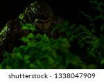 Stock photo bigfoot peeking through foliage on a black background with colored gels 1338047909