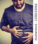 man having huge stomach pain... | Shutterstock . vector #1338233066