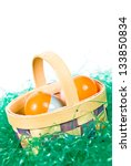 Easter basket with colorful eggs sitting on fake grass - stock photo