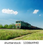 old train in green landscape under blue sky with clouds - stock photo