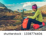 Trailhead Rest Stop. Young Caucasian Woman with Backpack on the Alpine Trail. Summer Time Hiking. - stock photo