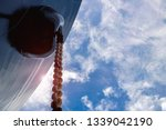 Small photo of Shipyard close up Front of Cargo ship with Big anchor chain hanging at forecastle deck during ship repair in floating dock on blue sky background.