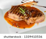 Small photo of Pepper steak with Gravy sauce. In a white plate on a wooden background. Making a good beef steak is considered a top flight in the culinary industry.