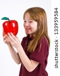Female school child holding a clear plastic apple - stock photo