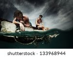 Two Men Floating In A Sea With...