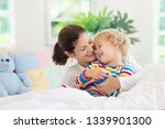 mother and child playing in bed ... | Shutterstock . vector #1339901300