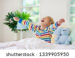 child playing in bed in white... | Shutterstock . vector #1339905950