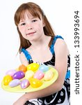 Young Caucasian female child holding a plate of Easter eggs - stock photo