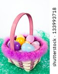 Easter basket with colorful eggs sitting in artificial grass - stock photo