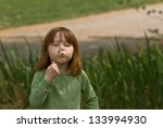 Young Caucasian girl blowing dandelion seeds - stock photo