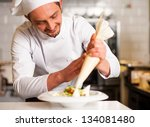 Professional male chef in restaurant kitchen decorating the dish. - stock photo
