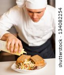 Chef pouring mayonnaise sauce on vegetable salad with brown bread sandwich. - stock photo