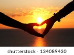 Stock photo two hands of lovers on the background of sunset on the sea 134089430