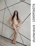alluring model in beige laced... | Shutterstock . vector #1340956076