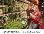 young couple in grocery store.... | Shutterstock . vector #1341523730