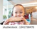 little asian boy eating whole... | Shutterstock . vector #1341738470
