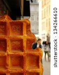 Big waffel on the road with blurred cityscape on background - stock photo