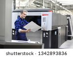 Small photo of Offset printing. The printer checks the printout. Printer in the printing house.