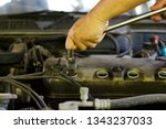 Hand use Wheel wrench with sparkplug wrench to Remove the spark plug for Repair Valve cover oil leaked