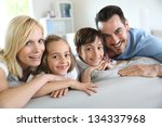 family of four sitting in sofa... | Shutterstock . vector #134337968