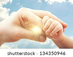Small photo of concept of love and family. hands of mother and baby on the sky