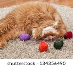 Stock photo red fluffy cat playing with colored balls of yarn on a carpet 134356490