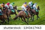 Stock photo group of jockeys and race horses racing on track 1343617463