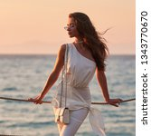Small photo of Young stylish woman in white blouse, trousers and sunglasses standing at sea coast and enjoying tropical sunset. Elegant rich girl looking away