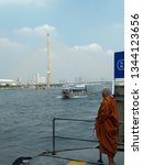 Small photo of Bangkok, Thailand - 12/21/2016: Thai Monk is waiting inline at the pier, for the boat to get across Chao Phaya River to Wat Arun.