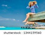 woman sitting on wooden beach... | Shutterstock . vector #1344159560
