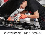 mechanic is pouring oil into... | Shutterstock . vector #1344299600