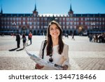 Small photo of Young happy woman exploring center of Madrid. visiting famous landmarks and places.Cheerful female traveler at famous Plaza Mayor square admiring statue of Philip III.Spain travel experience.
