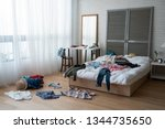 Small photo of modern bright bedroom with messy clothes scatter on white bed and floor. empty room with nobody in cozy apartment. packing luggage suitcase for summer vacation and spring holidays concept lifestyle.